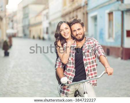 beautiful young couple on a bicycle in the city smiling with positivity casual dressed - stock photo