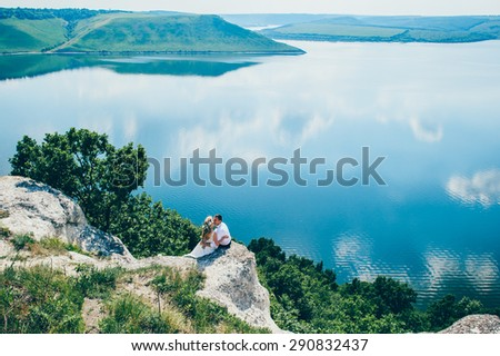 beautiful young couple posing on the rock near the lake  - stock photo