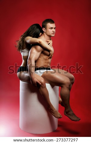 Beautiful young couple posing over red background. Studio shot. Conceptual photo. - stock photo