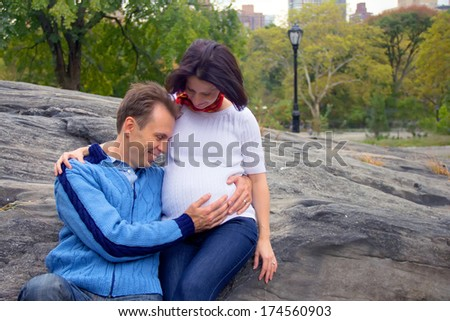 Beautiful young couple: pregnant  woman and her happy husband  - stock photo