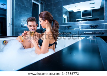 Beautiful young couple relaxing together and drinking Champagne in the Whirlpool.