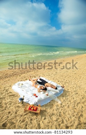 Beautiful young couple resting in bed in morning on the beach - stock photo