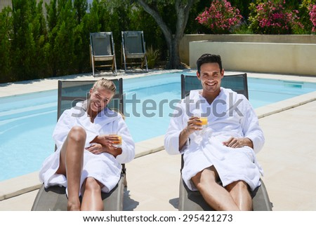 beautiful young couple resting in deck chairs with bathrobe by the pool of a thalasso resort - stock photo