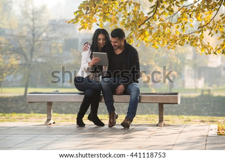 Beautiful Young Couple Sitting On Bench In The Park On A Beautiful Autumn Day - They Are Using Internet Via Digital Tablet - stock photo