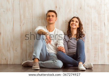 Beautiful young couple sitting on the wooden floor, smiling in everyday clothes at home - stock photo