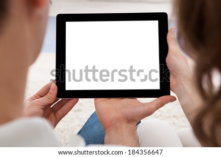 Beautiful young couple sitting side by side on a sofa looking at a tablet together - stock photo
