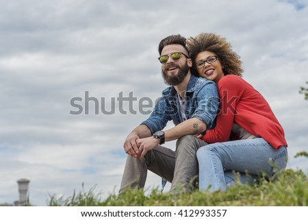 Beautiful young couple smiling at the park - stock photo
