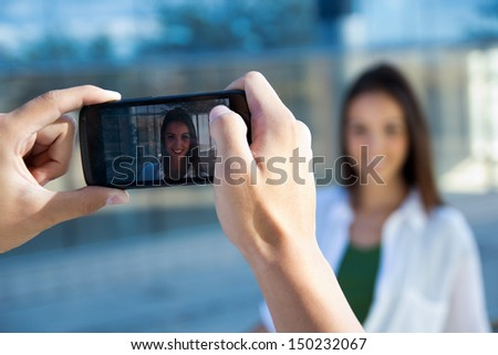 Beautiful young couple taking photos with mobile - stock photo