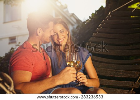 Beautiful young couple toasting wine outdoors. They are sitting on a hammock smiling and drinking wine with bright sunlight in backyard. Young man and woman spending quality time together on weekend. - stock photo