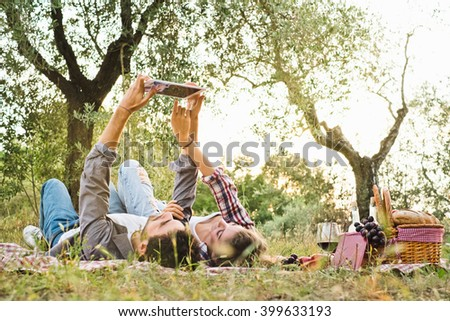Beautiful Young Couple Using Tablet During Picnic Outdoor - stock photo