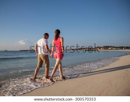 Beautiful young couple walking along the seashore, back view - stock photo