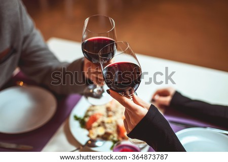 Beautiful young couple with glasses of red wine in luxury restaurant - stock photo