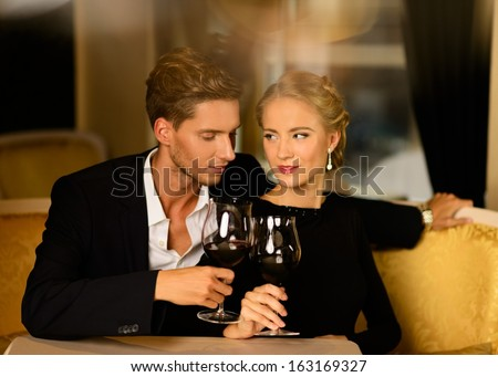 Beautiful young couple with glasses of wine in luxury interior - stock photo