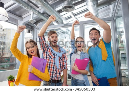 Beautiful young creative team is celebrating their success. They are standing and raising their fist up. The women are holding documents. The men are laughing - stock photo