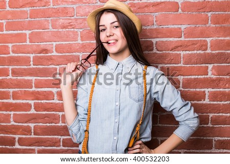 Beautiful young dark-haired girl in casual clothes posing, smiling, touching eyeglasses and showing OK, standing against brick wall - stock photo