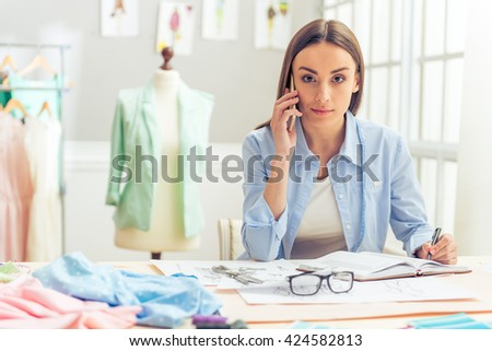 Beautiful young designer is talking on the mobile phone and looking at camera while working in dressmaking studio - stock photo