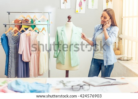 Beautiful young designer is talking on the mobile phone and smiling while examining her work in dressmaking studio - stock photo