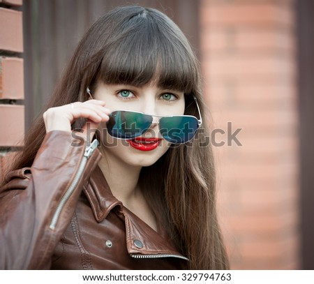 Beautiful young elegant woman face, has haired nature hair, happy fun smile, blue eyes, sunglasses, brown leather jacket, sexy lips. Pure makeup.  - stock photo