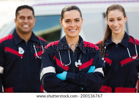 beautiful young EMT and colleagues in front of ambulance - stock photo