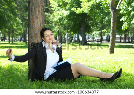 Beautiful young entrepreneur in park stretching during planning work - stock photo