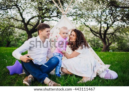 Beautiful young family in the nature - stock photo