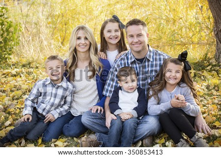 Beautiful Young Family Portrait with fall colors in the background - stock photo
