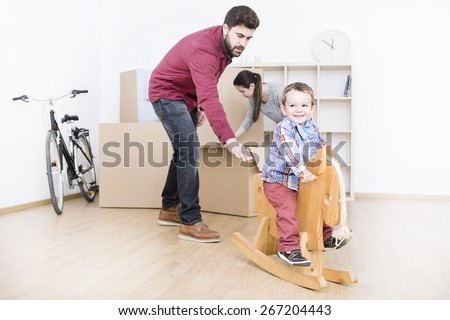 beautiful young family unpacking in new home, and the child playing with a wooden horse - stock photo