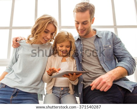 Beautiful young family using tablet and smiling while sitting near the window at home - stock photo