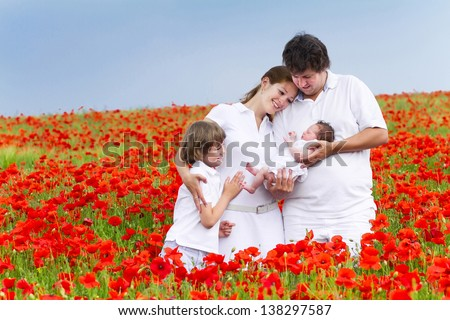 Beautiful young family with two children in a red flower field - stock photo