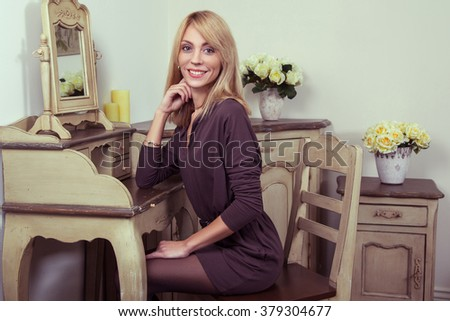 Beautiful young fashion caucasian 30-35 years blonde model in brown dress and black shoes and fair hairstyle posing near the secretaire and looking at camera in provence design interior.. - stock photo