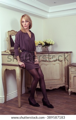 Beautiful young fashion caucasian 30-35 years blonde model in brown dress and fashion makeup and hairstyle and fair hair posing near the secretaire and looking at camera in provence design interior.. - stock photo