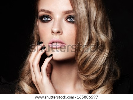 Beautiful young fashion model with smoky eyes and black manicure - stock photo