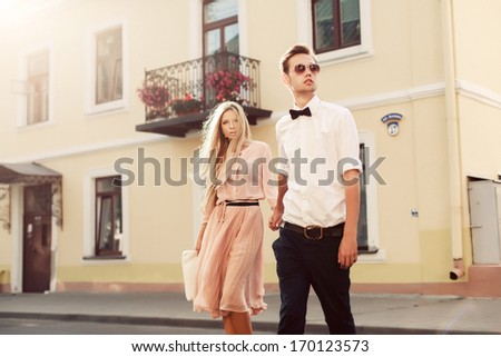 Beautiful young fashion stylish couple walking on the street in city old town together in summer evening ready to night party and have fun with love - stock photo