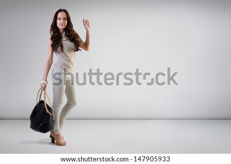 Beautiful young fashion woman posing at studio with bag, full length portrait - stock photo
