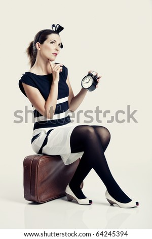 Beautiful young fashion woman sitting over a suitcase and holding a clock - stock photo