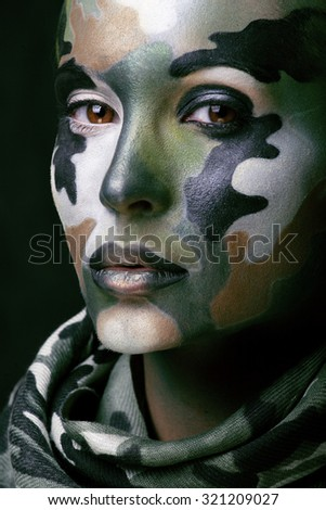 Beautiful young fashion woman with military style clothing and face paint make-up, khaki colors, halloween celebration swag - stock photo