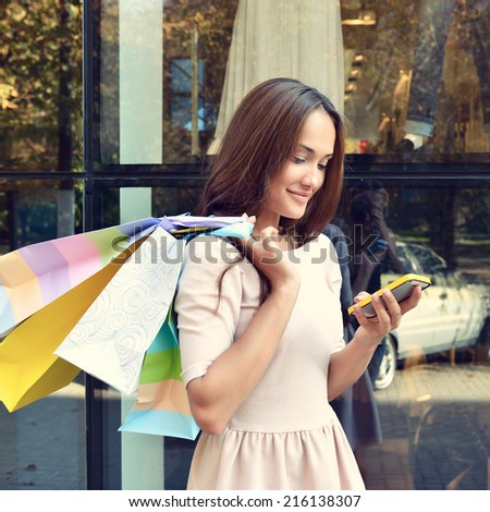 Beautiful young fashion woman with shopping bags near shop window calling smart phone, toned - stock photo
