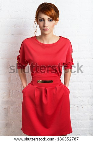 Beautiful young fashionable woman posing in red dress, smiling, looking at camera.  - stock photo