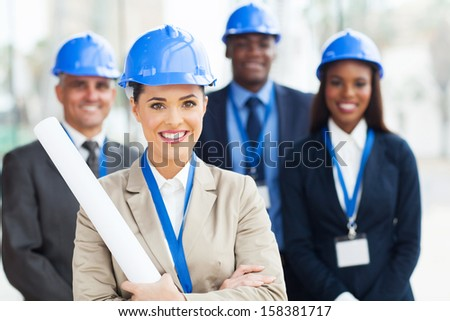 beautiful young female architect with colleagues on background - stock photo