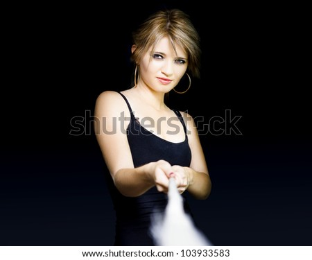 Beautiful young female business person pulling rope in a business challenge and tug of war concept on dark background - stock photo