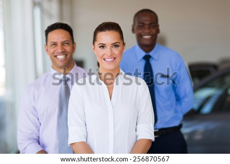 beautiful young female car dealer with colleagues on background - stock photo
