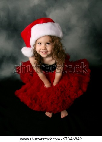 Beautiful young female child wearing a santa hat and red tutu skirt - stock photo