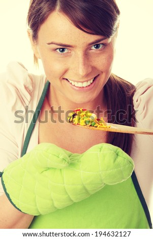 Beautiful young female cook tasting some food - stock photo