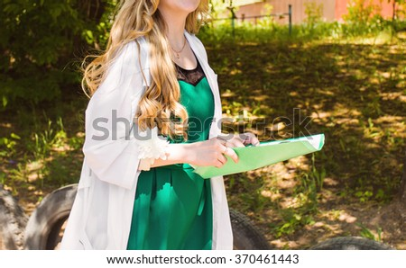 beautiful young female doctor in medical gown holding a medical records. nurse with  medical records - stock photo