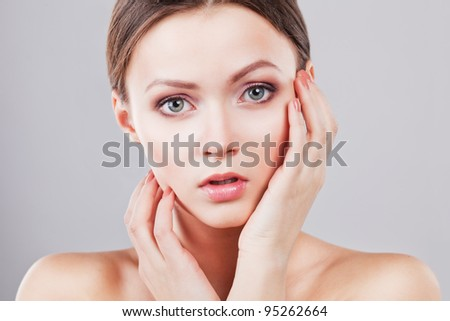 Beautiful young female face with fresh clean skin - stock photo
