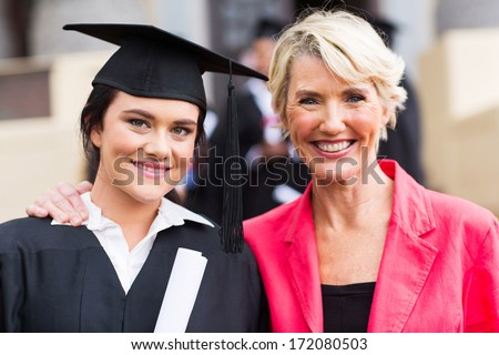 beautiful young female graduate and mother at graduation ceremony - stock photo