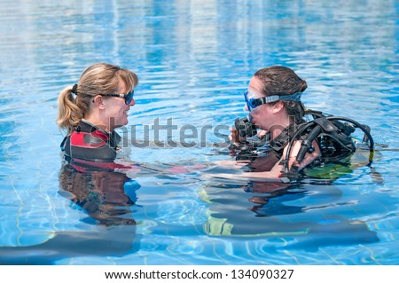 Beautiful young female learning to scuba dive - stock photo