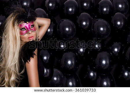 beautiful young female model in a carnival mask with feathers standing against the black balloons and sensually looks at the camera, wearing ball gowns prom evening dress with mesh and amazing makeup - stock photo