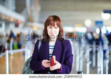 Beautiful young female passenger at check-in counter in the airport - stock photo