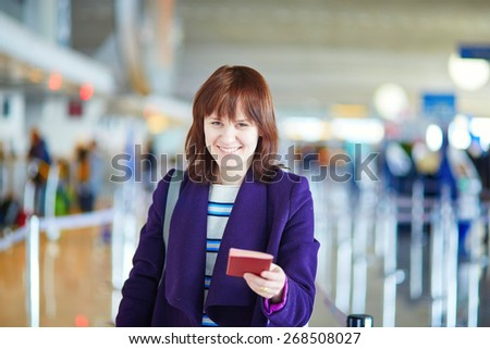 Beautiful young female passenger at check-in counter in the airport, holding her passport and boarding pass - stock photo